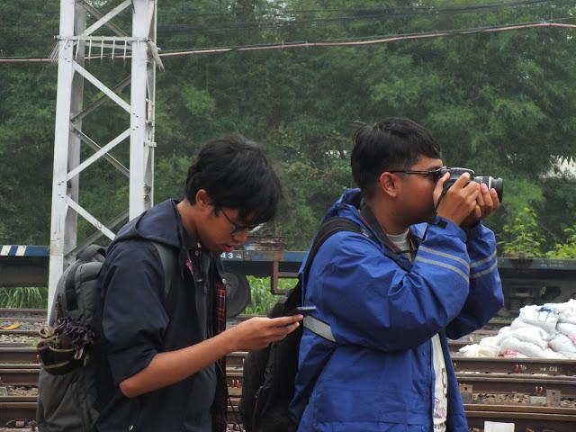 Ilustrasi pecinta kereta api yang memotret di stasiun