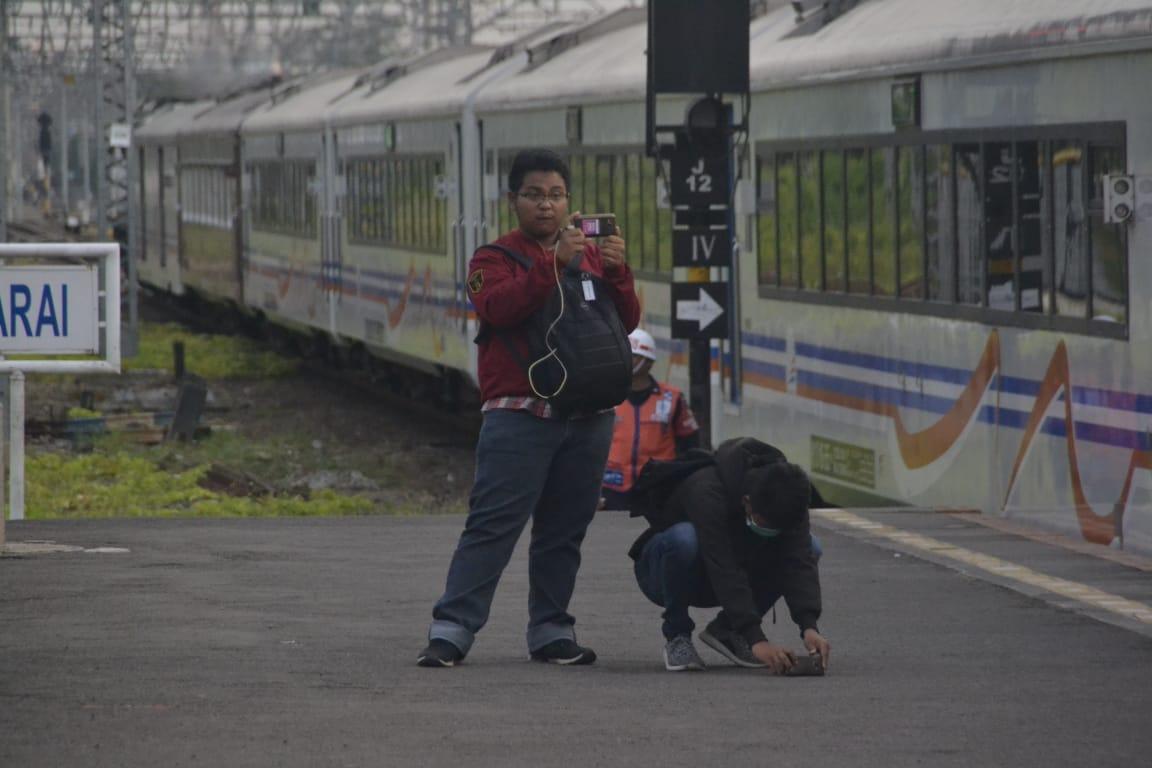 Railfans menjaga jarak aman