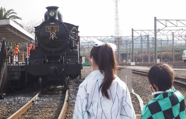 Dua orang anak yang ber-cosplay karakter dari anime Kinmetsu no Yaiba saat berfoto di depan kereta wisata tematik